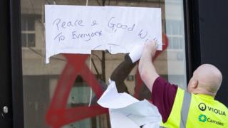 A council worker cleans the graffiti off a shop window in Belsize Park, North London