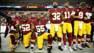 Washington Redskins players, some kneeling, during the anthem before a game against the Oakland Raiders