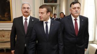 French President Emmanuel Macron (C) walks with Libyan Prime Minister Fayez al-Sarraj (R) and General Khalifa Haftar (L), commander in the Libyan National Army (LNA),
