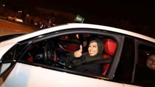 A woman drives a car and gives a thumbs up in Al Khobar, Saudi Arabia