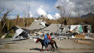 people ride a horse passed a destroyed building