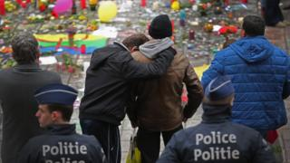 People react as they pay their respects at the Place De La Bourse in honour of the victims of yesterdays' terror attacks on 23 March 2016 in Brussels, Belgium