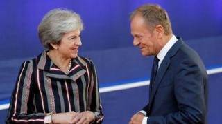 European Council President Donald Tusk and Britain's Prime Minister Theresa May talk on 19 October