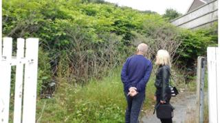 Robin Waistell showing Eye on Wales presenter Nellie Bird the Japanese knotweed next to his property