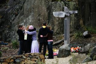 A family embraces at the Port Arthur memorial site during a commemoration service to mark the 10th anniversary of the massacre 28 April 2006 in Port Arthur, Australia