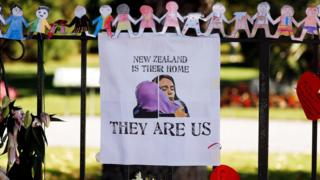 "A poster hangs at a memorial site for victims of Friday""s shooting, in front of Christchurch Botanic Gardens in Christchurch, New Zealand"