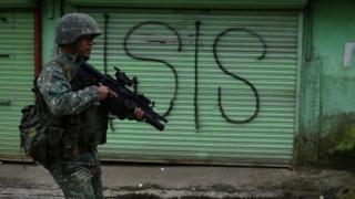 A Philippine Marine walks past graffiti during a patrol along a deserted street at the frontline in Marawi, on the southern island of Mindanao on 22 July 2017.