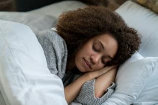 Imagem mostra mulher jovem dormindo numa cama