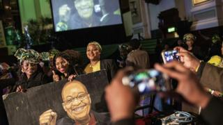 South African governing party African National Congress (ANC) members and supporters pose with a portrait of South African and ANC President Jacob Zuma during a campaign event at the Johannesburg Town Hall in Johannesburg, South Africa - Wednesday 27 July 2016