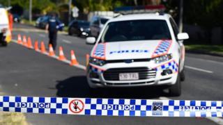 A Queensland Police car outside a crime scene