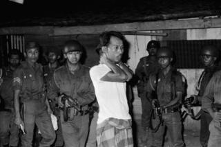 A suspected sympathizer with the Communist-led abortive coup of October 1th is questioned under gunpoint. The Indonesian Army is continuing its careful screening in an effort to uproot dissenters.