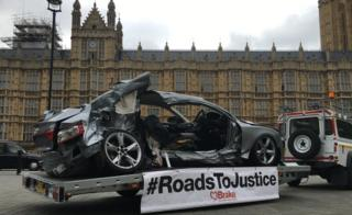 A wrecked car on a trailer outside the Palace of Westminster