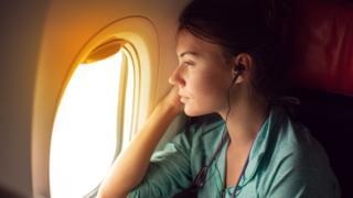 Mulher sentada dentro de um avião, olhando pela janela com fones de ouvido