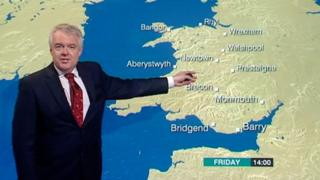 Carwyn Jones in front of a BBC weather map