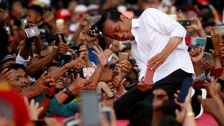 Indonesia's presidential candidate for the upcoming general election Joko Widodo takes pictures with his supporters during his first campaign rally at a stadium in Serang, Banten province, Indonesia, March 24, 2019