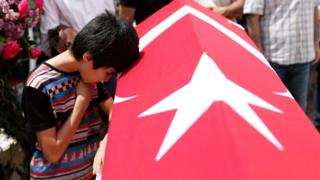 Relatives of a victim of the attack at Istanbul's airport mourn during a funeral on 30 June