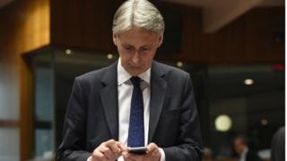 Chancellor Philip Hammond on phone