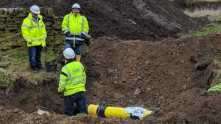Three engineers repairing damage to a gas pipe