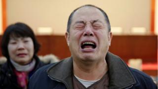 Wen Wancheng, whose son was among passengers onboard Malaysia Airlines flight MH370, cries as relatives arrive for a meeting with the airline representatives in Beijing, China, 18 January 2017.