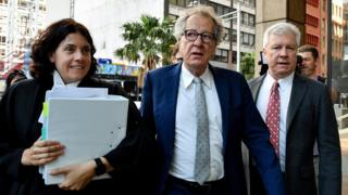 Actor Geoffrey Rush (centre) arrives at the Federal Court in Sydney