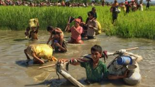 Rohingya children and adults wade through water carrying their possessions