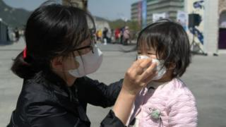 A woman helps a child put on a face mask in Seoul