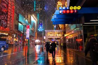 People walk to work in midtown Manhattan during a storm.