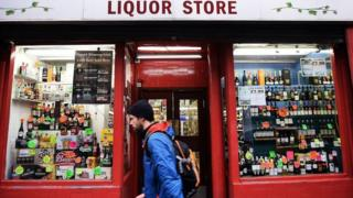 A man walks past a shop selling alcohol