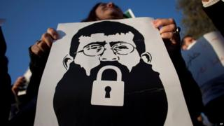 A Palestinian woman holds a poster with a drawing depicting Khader Adnan, who went on hunger strike in detention
