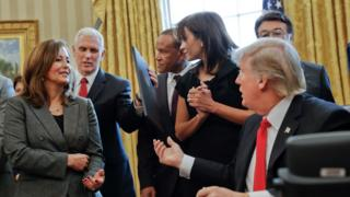 President Donald Trump hands off an executive order to Vice President Mike Pence, left, after signing the order in the Oval Office of the White House in Washington, Monday, Jan. 30, 2017, surrounded by small business leaders.
