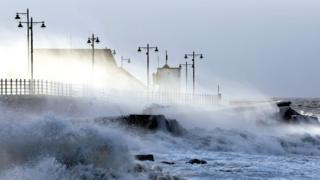 Waves breaking over sea wall with houses behind