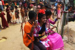 Young Rohingya refugees enjoy a ride on a carousel during Eid Al-Adha festival celebrations.
