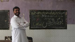 Abdul Wahid Shaikh stands near a blackboard in the school where he teaches