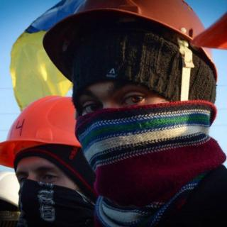 Учасник демонстрації в балаклаві з каскою
