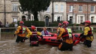 Woman taken to safety in a dinghy during flooding in York in December 2015