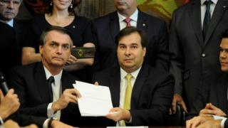 Brazil's President Jair Bolsonaro and Lower House President, Rodrigo Maia pose with the proposal of the pension system reform bill at the National Congress in Brasilia, Brazil February 20, 2019