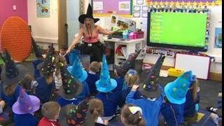 A class of children wearing witches hats listening to their teacher read a story