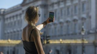 A woman playing Pokémon Go outside Buckingham Palace