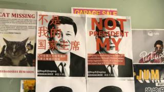 "Posters reading ""not my president"" in Chinese and English over a photo of Xi Jinping at Melbourne University in Australia"