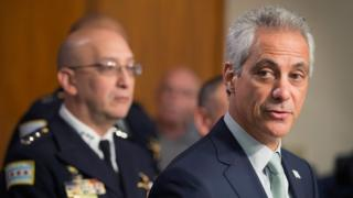 Interim Chicago Police Superintendent John Escalante (L) listens as Chicago Mayor Rahm Emanuel speaks of planned changes in training and procedures for Chicago police in the wake of recent shootings.