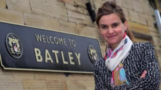 Jo Cox standing next to Batley sign