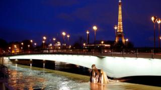 The Eiffel Tower with raised water levels at the Zouave statue of the Pont d'Alma bridge