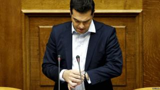 Greek Prime Minister Alexis Tsipras looks at his watch as he delivers a speech during a parliamentary session in Athens on 28 June 2015