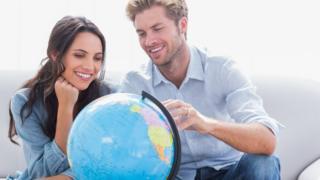 رجل وامرأة ينظرون إلى كرة تمثل الكرة الأرضية وخريطة العالم