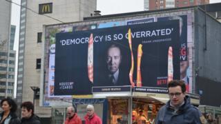 """Rotterdam'daki bir binanın cephesinde yer alan seçim afişlerinin üzerine """"Demokrasi çok abartıldı"""" sloganıyla House of Cards dizisinin reklamı yer alıyor"""