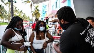 positive people A security guard checks the temperature of a woman at the entrance of a restaurant on Ocean Drive in Miami Beach, Florida on June 24, 2020