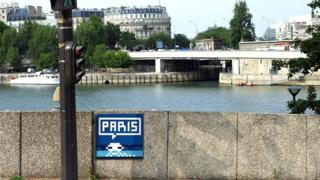 A picture of Invader's street art - a space invader with the words Paris above it