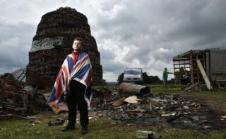 Having finished school for the summer, Tyler Reid helps guard the Lisburn bonfire.