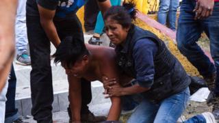 Un hombre y una mujer lloran en el lugar del siniestro.