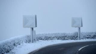 Road signs are covered with snow on the A628 Woodhead Pass in the Longdendale Valley in Derbyshire's High Peak